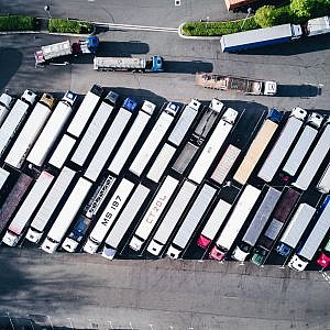 Aerial shot of dozens of lorries parked, potentially with manipulated tachographs